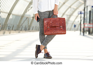 woman holding leather bag and mobile phone