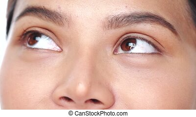 Cropped portrait of woman over white background extreme closeup. Closeup woman looking up and into the camera - video in slow motion