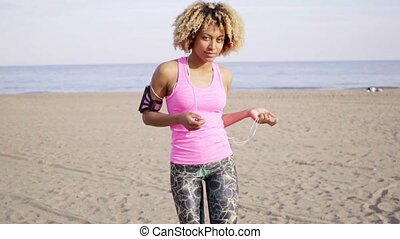 Cropped rear view of woman running on beach - Below shoulder...