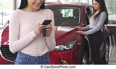 Cropped shot of a female driver using her smart phone