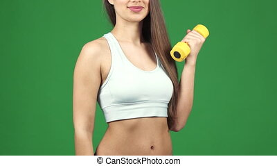 Cropped shot of a happy sportswoman with a dumbbell holding...