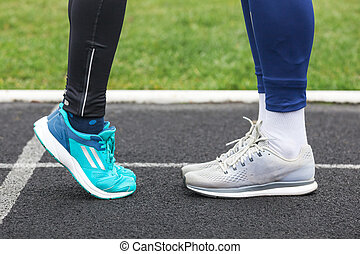 Cropped shot of a male and female legs in running shoes close to each other.