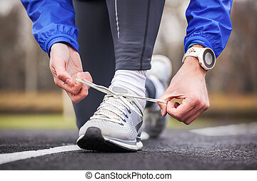 Cropped shot of a man tying his shoelaces on running shoes.