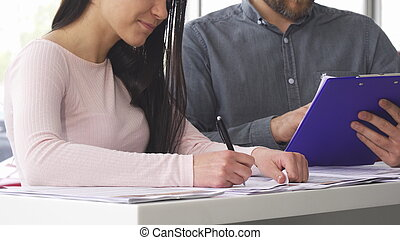 Cropped shot of a woman signing papers with the salesman at the car salon