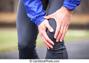 Cropped shot of a young runner holding his injured knee while running.