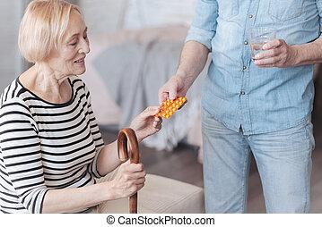 Cropped shot of careful husband brining his wife pills