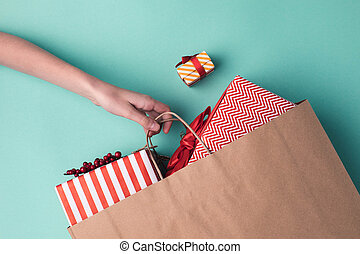 hand holding paper bag with presents