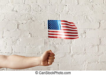 cropped shot of man holding american flagpole against white brick wall