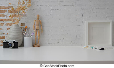 Cropped shot of workspace with copy space, camera, frame, painting tools, wooden figure and vase on withe desk with brick wall