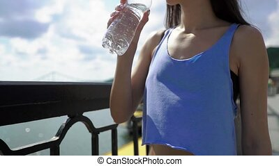 Cropped side shot view of a young charming brunette female jogger holding bottle of water while resting after active run outdoors