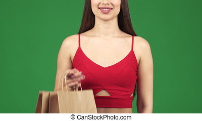 Cropped studio shot of a woman smiling holding shopping bags...