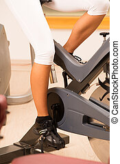 Cropped view of a young woman using an exercise bike in the gym