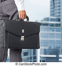 Cropped view of businessman holding a briefcase in the...