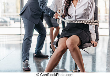 cropped view of businesswoman bound with rope on chair and...