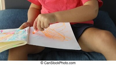 cropped view of cute kid drawing on paper with pencils while...