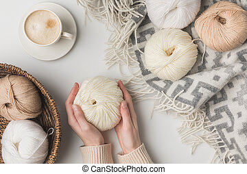 cropped view of woman holding cup of coffee and yarn balls on blaket and in basket on white background