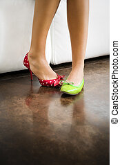 mismatched shoes - Cropped view of woman wearing mismatched...