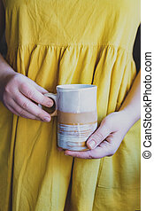 Cropped young white woman in a simple yellow linen dress holds in her hands a clay ceramic cup of an original handmade shape. Copy space. Trend
