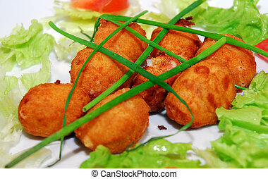 croquettes of ham on a plate garnished with lettuce