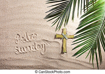 Cross and Palm Tree Leaves on sand. Palm sunday concept.
