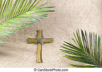 Cross and Palm Tree Leaves on sand. Palm sunday concept. Top view