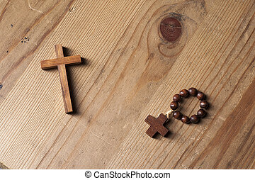 Cross and rosary over wood table with window light
