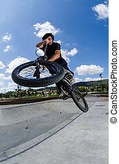 Cross bar - BMX rider jumps while doing cross bar trick.