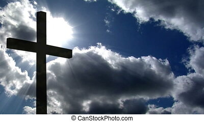 10697 A cross silhouette in front of time lapse cloud and sunlight.