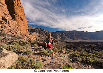 Cross country running with backpack in mountains on rocky trail