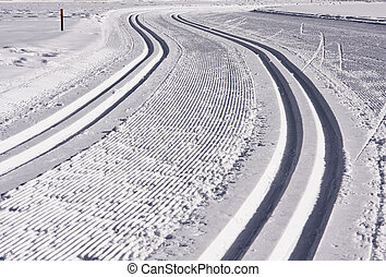 A cross-country ski track in Aspen forms an S-shaped trail that disappears into the distance. The parallel lines of the groomed path and the more deeply indented ski tracks give this image some shape.
