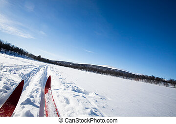 Cross Country Skies - A cross country skiier skiing off...