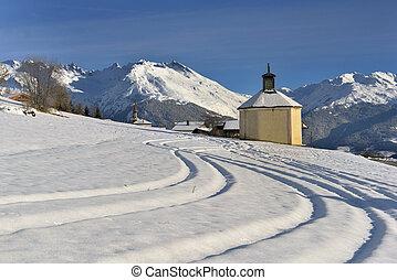 little chapel in a beautiful snowy mountain landscape