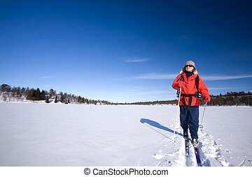 Cross Country Skiing - A woman cross country skiing across a...