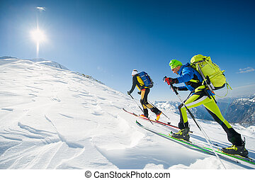 Cross country skiing team couple of men towards the summit of the mountain