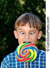 cross eyed boy eating lollipop