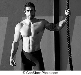 Cross fit gym man holding hand a climbing rope