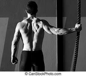 Cross fit gym man holding hand a climbing rope rear view