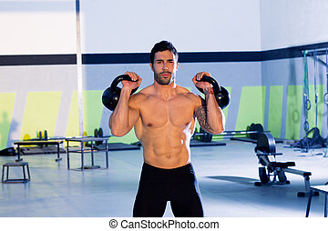 Cross fit man lifting kettlebell workout exercise at gym