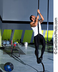 Cross fit rope climb exercise in fitness gym