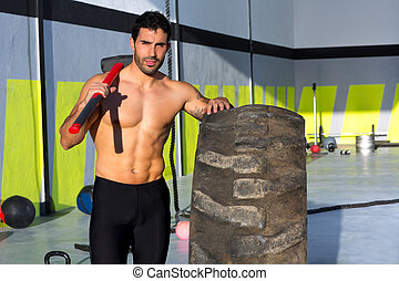 Cross fit sledge hammer man at gym relaxed