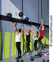 Cross fit workout people group with wall balls and rope