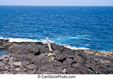 cross for a dead man on a rock at the sea