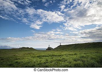 Cross in landscape of Ynys Llanddwyn Island with Twr Mawr lighthouse in background with blue sky
