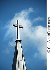 Cross in the Clouds - Christian cross on steeple against...