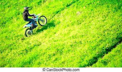 Cross motorcycle moving uphill on the grass hill. Slow motion shot