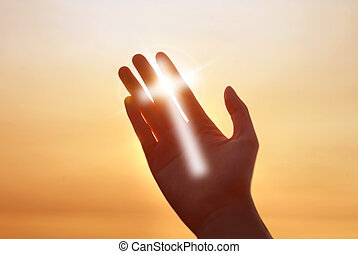 Cross of light on human hand concept of religion