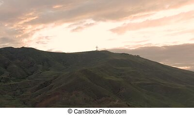 Cross on a mountain at sunset in Georgia Rustavi city