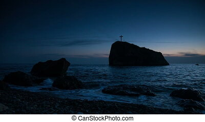 Cross on a rock in the sea, on the coast in the evening