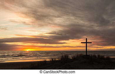 Cross on a sand dune with a wonderful setting sun in the background.