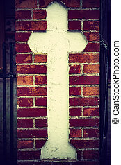 cross on brick wall of the old church